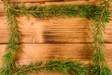 Frame of the fir tree branches on rustic wooden table
