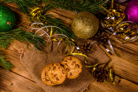 Stack of chocolate chip cookies on sackcloth in front of christmas decorations Stock Photo