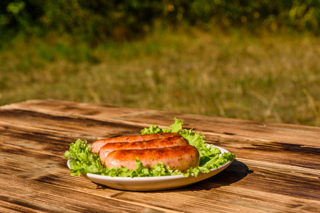 Ceramic plate with grilled sausages and lettuce leaves on rustic wooden table