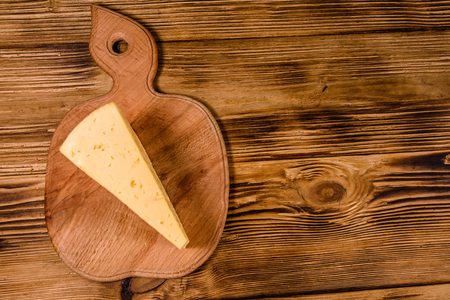 Cutting board with piece of cheese on rustic wooden table. Top view