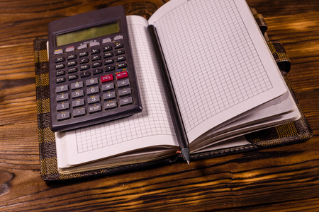Opened notepad, scientific calculator and pencil on rustic wooden table