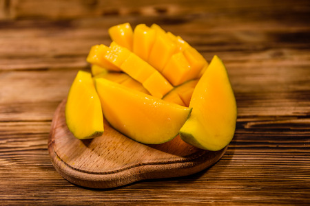 Cutting board with chopped mango fruit on rustic wooden table