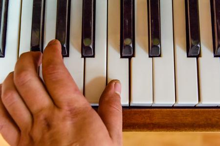 Child hand on a shiny piano keys. Top view Foto de archivo