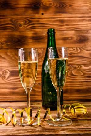 Bottle of champagne and two wineglasses decorated with golden ribbon on rustic wooden table Banco de Imagens