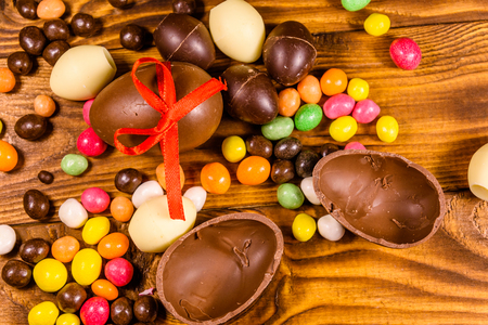 Chocolate easter eggs and multicolored candies on rustic wooden table. Top view