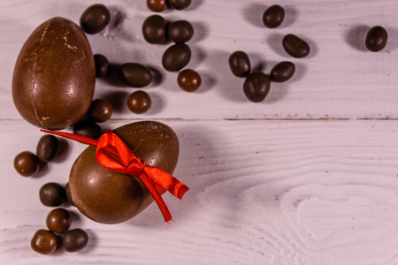 Chocolate easter eggs on white wooden table. Top view