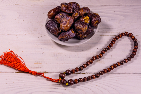 Date fruits and rosary on white wooden table Foto de archivo