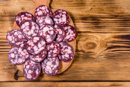 Cutting board with sliced salami sausage on rustic wooden table. Top view 版權商用圖片