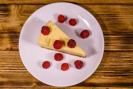 White plate with cheesecake New York and raspberries on rustic wooden table. Top view