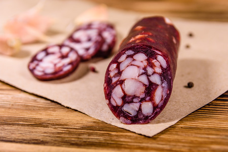 Sliced salami sausage and garlic on brown wrapping paper