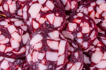 Background of many sliced pieces of salami sausage