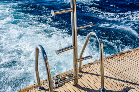 Metal staircase for descent into the water and wave trace with white foam on water surface behind of fast moving yacht