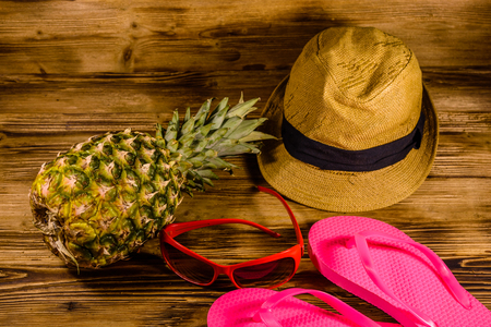 Pineapple, straw hat, sunglasses and flip flops on rustic wooden table. Summer vacations