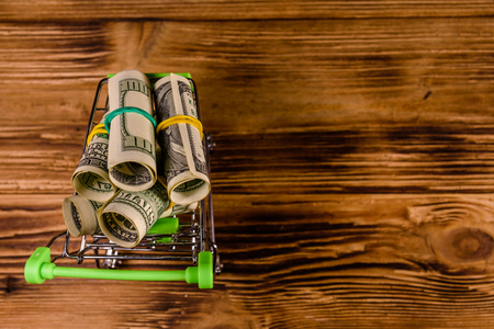 Small shopping cart with rolled up one hundred dollar banknotes on wooden background. Top view