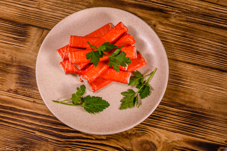 Ceramic plate with pile of crab sticks and parsley twig on wooden table. Top view