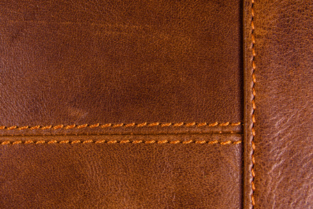 Texture of natural brown leather and stitches Фото со стока