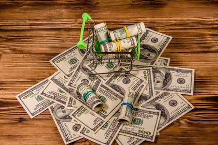 Small shopping cart with rolled up one hundred dollar banknotes on wooden background