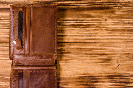 Opened brown leather wallet on rustic wooden table. Top view
