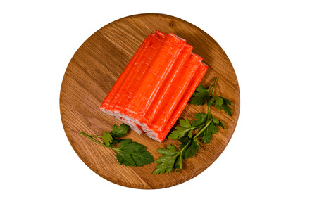 Cutting board with pile of crab sticks and parsley twig isolated on white background