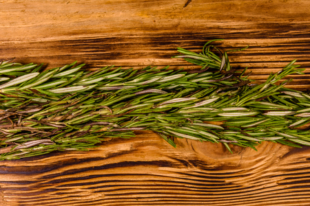 Stem of the rosemary on rustic wooden table. Top view