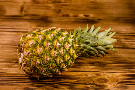 Whole ripe pineapple on rustic wooden table. Top view 版權商用圖片