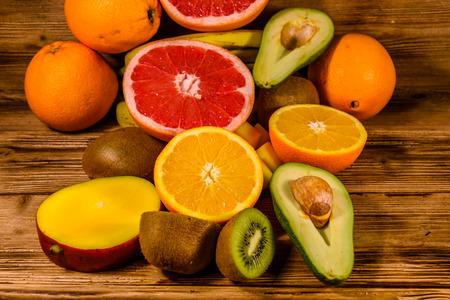 Still life with exotic fruits. Mango, oranges, avocado, grapefruit and kiwi fruits on rustic wooden table 版權商用圖片