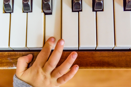 Child hand on a shiny piano keys. Top view