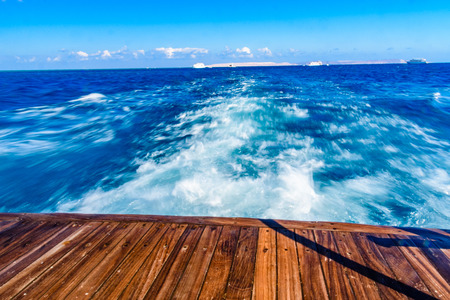 Wave trace with white foam on water surface behind of fast moving yacht