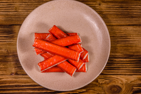 Ceramic plate with pile of crab sticks on wooden table. Top view 免版税图像