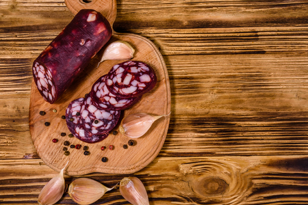 Cutting board with sliced salami sausage on rustic wooden table. Top view Reklamní fotografie
