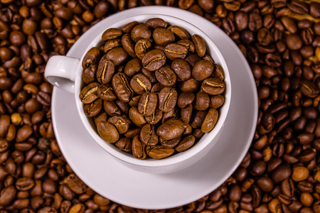 White cup filled with coffee beans on rustic wooden table. Top view Foto de archivo - 122780501