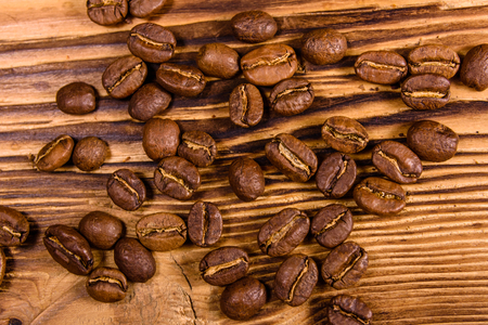 Scattered coffee beans on rustic wooden table. Top view Foto de archivo - 122780502