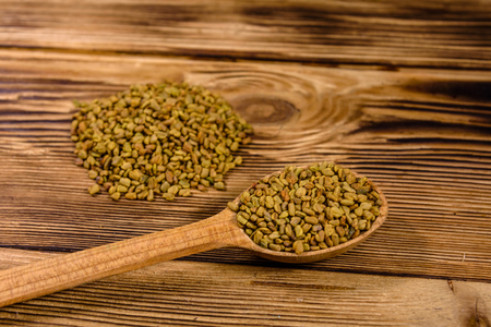 Spoon with fenugreek seeds on rustic wooden table Imagens