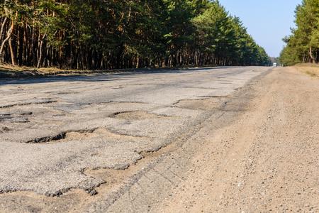 Grandes baches en una carretera asfaltada dañada Foto de archivo