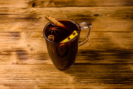 Cup of mulled wine with cinnamon on rustic wooden table Stock Photo