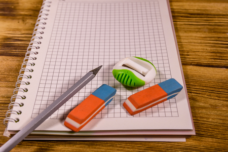 Open notepad and different stationeries on wooden table