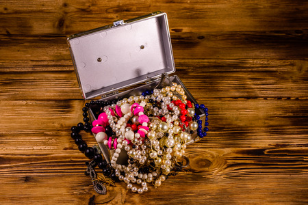 Aluminium case full of different jewelry on rustic wooden table