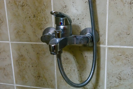 Closeup of chrome faucet in modern shower cabin