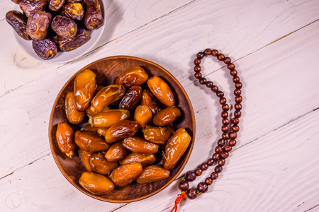 Date fruits and rosary on white wooden table. Top view