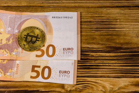 Fifty euro banknotes and bitcoins on wooden background. Top view Stock Photo