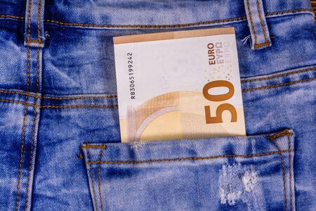 Fifty euro banknote in pocket of blue jeans
