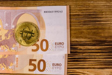 Fifty euro banknotes and bitcoins on wooden background. Top view