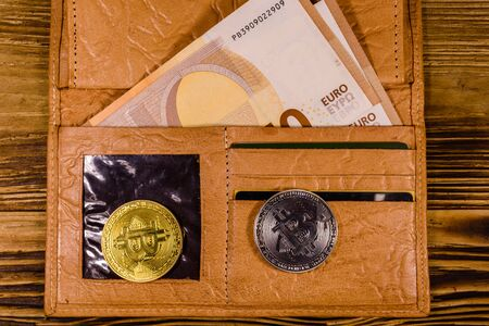 Brown leather wallet with fifty euro banknotes and bitcoins on wooden background. Top view