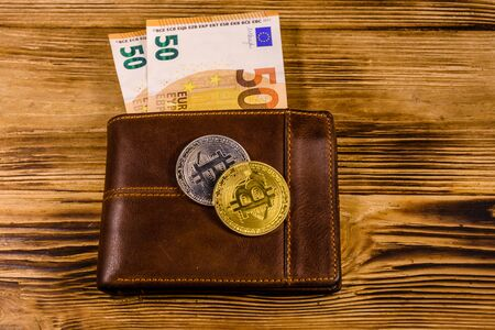 Brown leather wallet with fifty euro banknotes and bitcoins on wooden background Stock Photo