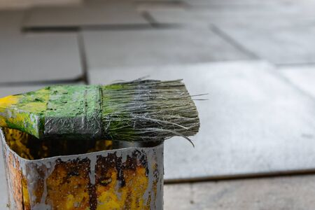 Dirty green paintbrush on chipboard. House renovation
