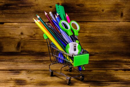 Small shopping cart with different school stationery on rustic wooden background. Back to school concept