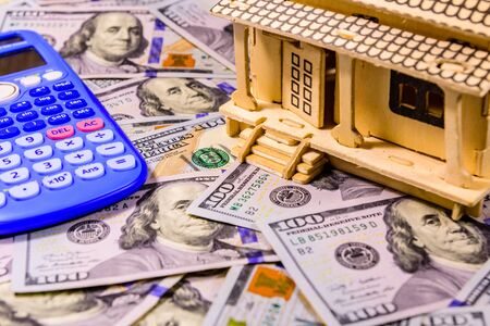 Plywood model of house, calculator and one hundred dollar banknotes. Loan, real estate concept Stock Photo