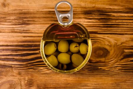 Opened tin can with green olives on rustic wooden table. Top view
