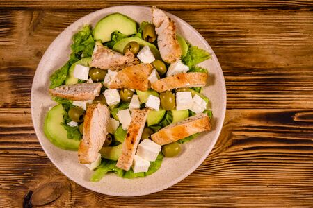 Fresh salad with chicken meat, feta cheese, avocado, green olives and lettuce leaves in ceramic plate on rustic wooden table. Top view Stock Photo