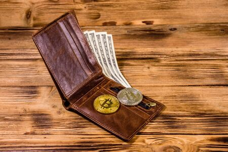 Brown leather wallet, bitcoins and one hundred dollar banknotes on wooden background Stock Photo